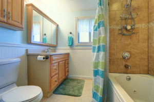 Sweet bathroom interior in soft blue and green tones. View of honey color cabinet with mirror shower and toilet.